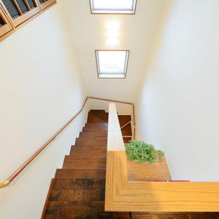 Imagen de escalera en U y papel pintado, de estilo de casa de campo, de tamaño medio, con escalones de madera, barandilla de madera y papel pintado