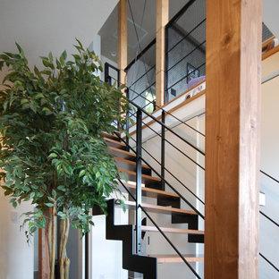 Ejemplo de escalera recta y papel pintado, rústica, de tamaño medio, sin contrahuella, con escalones de madera, barandilla de metal y papel pintado