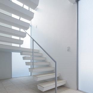 他の地域のタイルのコンテンポラリースタイルのおしゃれなスケルトン階段 (金属の手すり) の写真