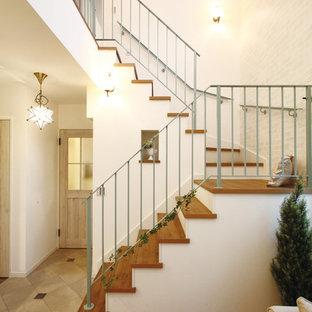 Ejemplo de escalera en L, romántica, con barandilla de metal y escalones de madera