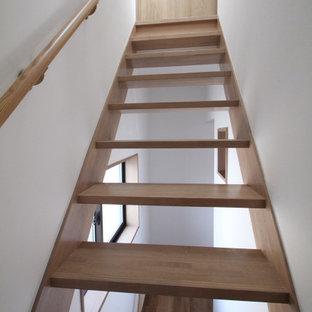 東京23区の小さい木の北欧スタイルのおしゃれな直階段 (木の蹴込み板、木材の手すり、壁紙) の写真