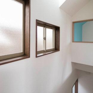 Ejemplo de escalera recta y papel pintado, nórdica, pequeña, con escalones de madera, barandilla de madera y papel pintado