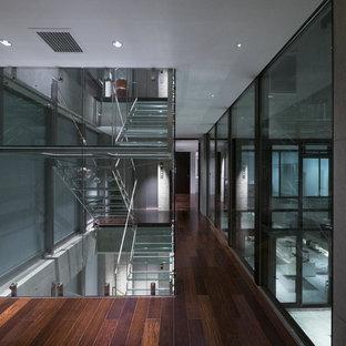 東京23区のガラスのインダストリアルスタイルのおしゃれな階段 (金属の手すり) の写真