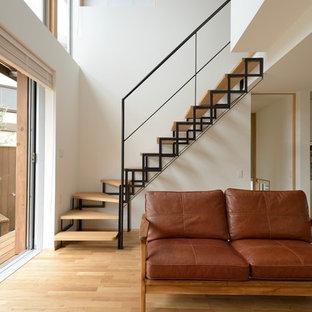 Foto de escalera en L, moderna, sin contrahuella, con escalones de madera y barandilla de metal