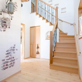 Ejemplo de escalera curva, de estilo zen, con escalones de madera, contrahuellas de madera y barandilla de varios materiales