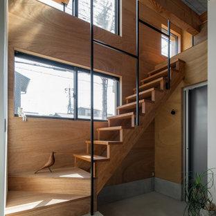 Foto di una piccola scala a rampa dritta etnica con pedata in legno, alzata in legno, parapetto in metallo e pareti in legno