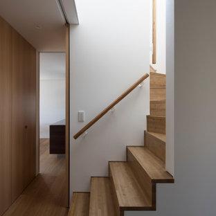 Cette photo montre un escalier moderne en U de taille moyenne avec des marches en bois, des contremarches en bois, un garde-corps en bois et du papier peint.