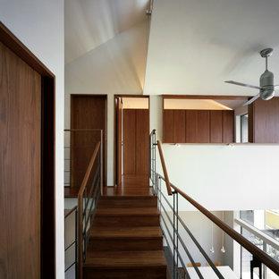 Idee per una scala curva moderna con pedata in legno, alzata in legno, parapetto in metallo e pareti in perlinato