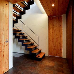 """Immagine di una scala a """"U"""" minimal di medie dimensioni con pedata in legno, nessuna alzata e parapetto in metallo"""