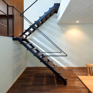 他の地域の広い木のコンテンポラリースタイルのおしゃれな折り返し階段 (木の蹴込み板、金属の手すり) の写真