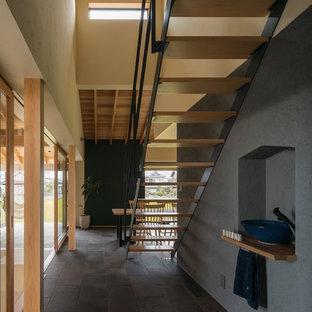 Immagine di una scala a rampa dritta etnica di medie dimensioni con pedata in legno, alzata in legno e parapetto in metallo