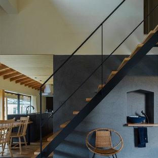 Ejemplo de escalera recta, de estilo zen, de tamaño medio, sin contrahuella, con escalones de madera y barandilla de metal