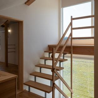 Foto de escalera en U y papel pintado, grande, sin contrahuella, con escalones de madera, barandilla de madera y papel pintado