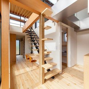 Esempio di una scala a rampa dritta etnica di medie dimensioni con pedata in legno, nessuna alzata e parapetto in metallo