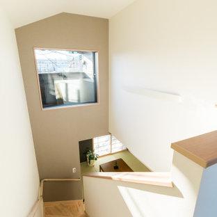 Foto de escalera en L y papel pintado, moderna, pequeña, con escalones de madera, contrahuellas de madera, barandilla de madera y papel pintado