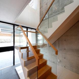 大阪の木のコンテンポラリースタイルのおしゃれな折り返し階段 (木の蹴込み板、ガラスの手すり) の写真