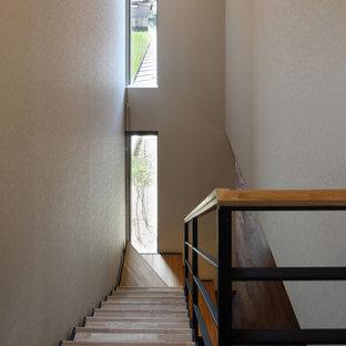 Foto de escalera en L y papel pintado, moderna, de tamaño medio, sin contrahuella, con escalones de madera, barandilla de madera y papel pintado