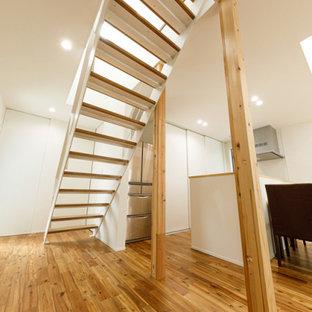 Ejemplo de escalera recta y papel pintado, minimalista, de tamaño medio, sin contrahuella, con escalones de madera, barandilla de metal y papel pintado