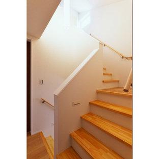 Imagen de escalera en U y papel pintado, moderna, con escalones de madera, barandilla de madera y papel pintado