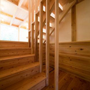 """Ispirazione per una scala a """"U"""" etnica di medie dimensioni con pedata in legno, alzata in legno e parapetto in legno"""