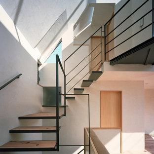 Imagen de escalera suspendida, de estilo zen, pequeña, sin contrahuella, con escalones de madera y barandilla de metal