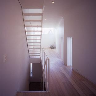 Ejemplo de escalera recta, moderna, pequeña, sin contrahuella, con escalones de madera y barandilla de metal