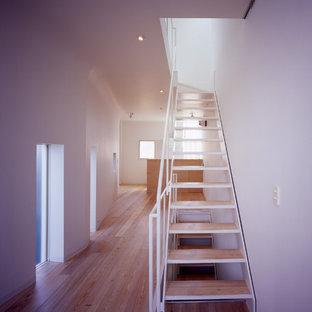 Imagen de escalera recta, moderna, pequeña, sin contrahuella, con escalones de madera y barandilla de metal