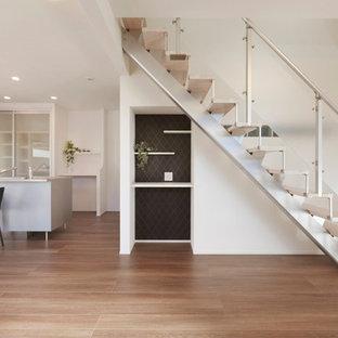 Ejemplo de escalera recta, minimalista, de tamaño medio, con escalones de madera y barandilla de metal