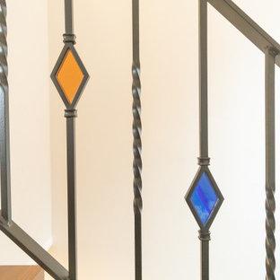 На фото: п-образная лестница в стиле лофт с металлическими перилами и обоями на стенах
