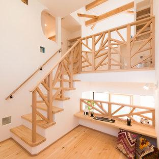 他の地域の木のコンテンポラリースタイルのおしゃれな階段 (フローリングの蹴込み板、木材の手すり) の写真