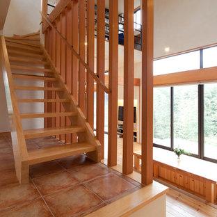 他の地域の木のカントリー風おしゃれな直階段 (木の蹴込み板、木材の手すり) の写真