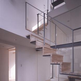 東京23区の木のコンテンポラリースタイルのおしゃれなフローティング階段 (木の蹴込み板、金属の手すり) の写真