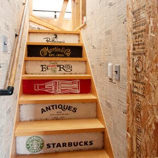 Ejemplo de escalera en L y papel pintado, industrial, con escalones de madera, contrahuellas de madera y papel pintado