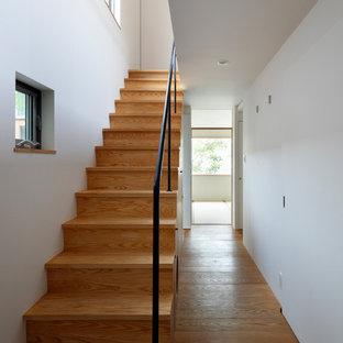 他の地域の木のモダンスタイルのおしゃれな直階段 (木の蹴込み板、金属の手すり) の写真