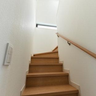 Пример оригинального дизайна: изогнутая лестница среднего размера в стиле модернизм с деревянными ступенями, деревянными подступенками, деревянными перилами и обоями на стенах