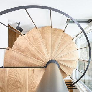 Ejemplo de escalera de caracol y papel pintado, contemporánea, de tamaño medio, sin contrahuella, con escalones de madera, barandilla de metal y papel pintado
