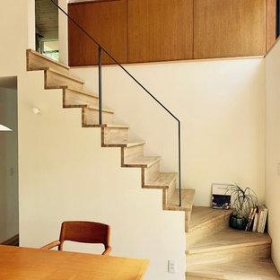 他の地域の中サイズの木のコンテンポラリースタイルのおしゃれな直階段 (木の蹴込み板、金属の手すり) の写真