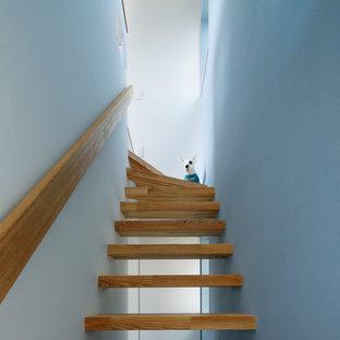 """Immagine di una scala a """"L"""" minimalista di medie dimensioni con pedata in legno e nessuna alzata"""