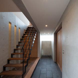 他の地域の中くらいの木のインダストリアルスタイルのおしゃれな階段 (金属の手すり) の写真