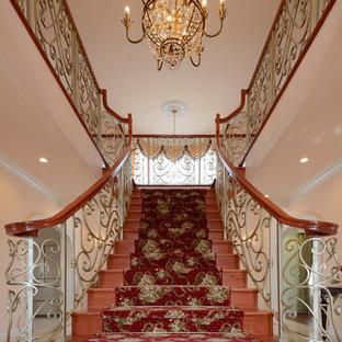 他の地域の巨大な木のトラディショナルスタイルのおしゃれな折り返し階段 (木の蹴込み板、木材の手すり) の写真