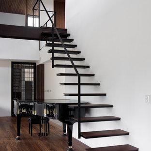 他の地域の木のトラディショナルスタイルのおしゃれな直階段 (金属の手すり) の写真