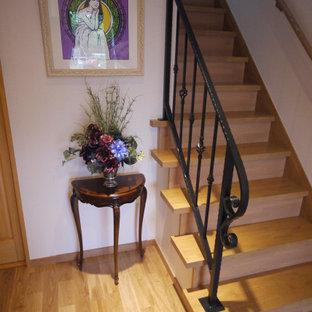 Modelo de escalera en U y papel pintado, tradicional, de tamaño medio, con escalones de madera pintada, contrahuellas de madera pintada, barandilla de metal y papel pintado