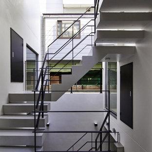 Diseño de escalera curva y machihembrado, contemporánea, de tamaño medio, con escalones de hormigón, contrahuellas de hormigón, barandilla de metal y machihembrado