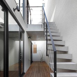 東京23区の広いコンクリートのモダンスタイルのおしゃれな階段 (金属の手すり) の写真