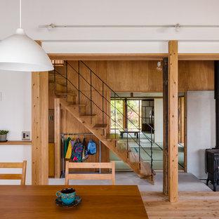 他の地域の木のアジアンスタイルのおしゃれな直階段 (木の蹴込み板、金属の手すり) の写真