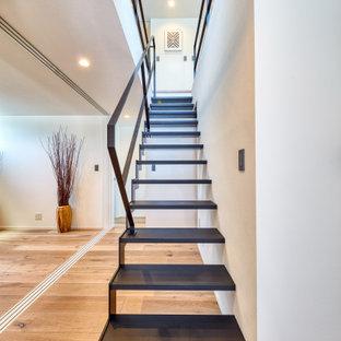 Ejemplo de escalera recta y papel pintado, marinera, grande, sin contrahuella, con escalones de madera, barandilla de metal y papel pintado