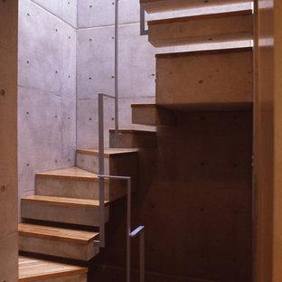 Ispirazione per una piccola scala a chiocciola moderna con pedata in legno, alzata in cemento e parapetto in metallo