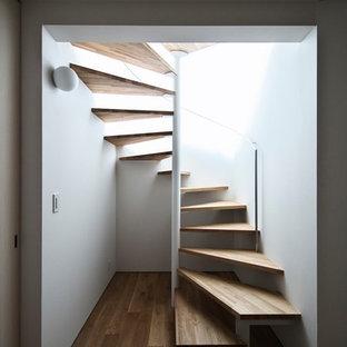 Ispirazione per una scala a chiocciola etnica con pedata in legno e nessuna alzata
