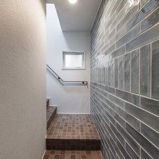Imagen de escalera en L, asiática, pequeña, con escalones con baldosas, contrahuellas con baldosas y/o azulejos y barandilla de metal