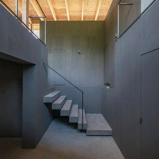Diseño de escalera recta, moderna, con escalones de hormigón, contrahuellas de hormigón y barandilla de metal